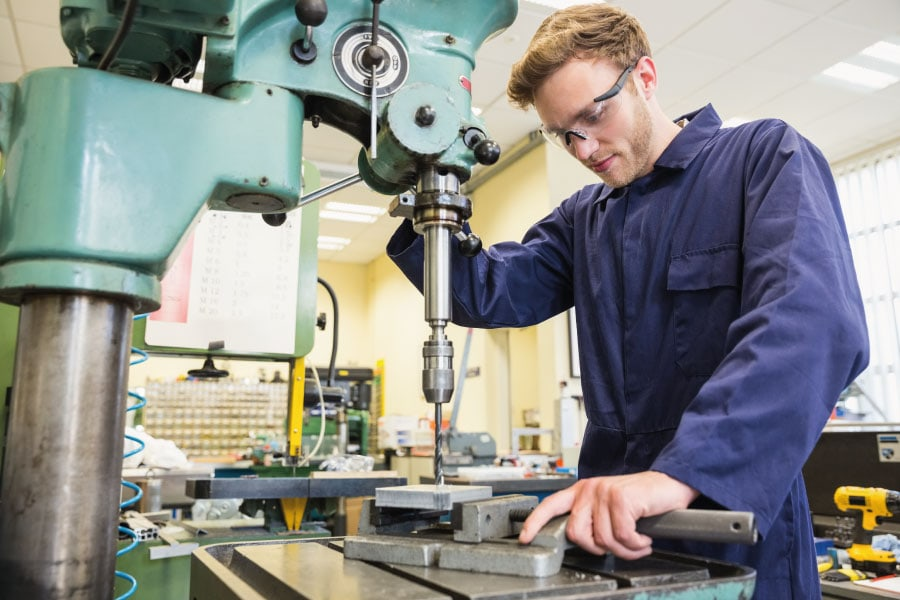 Engineering Apprentice using machinery in workshop