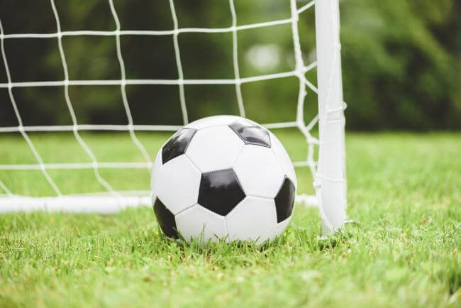 Football on grass in front of a goal net