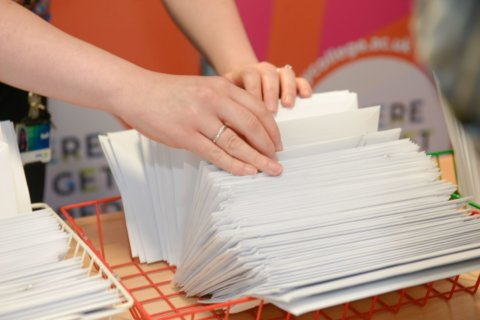Staff member sorting through stack of envelopes.