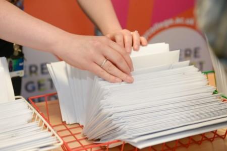 Staff member sorting through stack of envelopes.