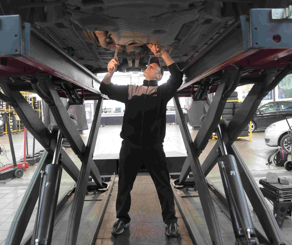 Technician working on vehicle.
