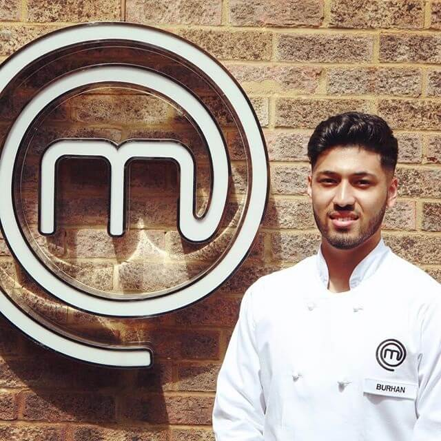 Burhan Ahmed standing in front of Master Chef logo