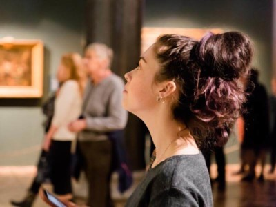 Woman looking at artwork in gallery space
