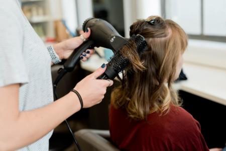 Woman holding hair dryer, drying customers hair.
